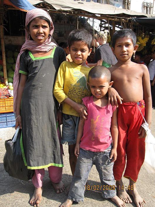 Tiggerbørn foran en frugtbod i Dhaka